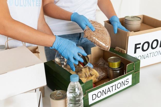 Volontari con guanti chirurgici che preparano casse di donazioni alimentari