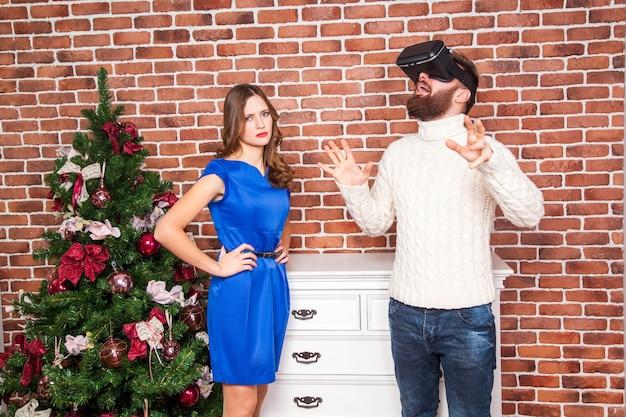 Tecnologia vr e conflitto di coppia. uomo che usa l'auricolare vr e sua moglie è arrabbiata per il nuovo anno.