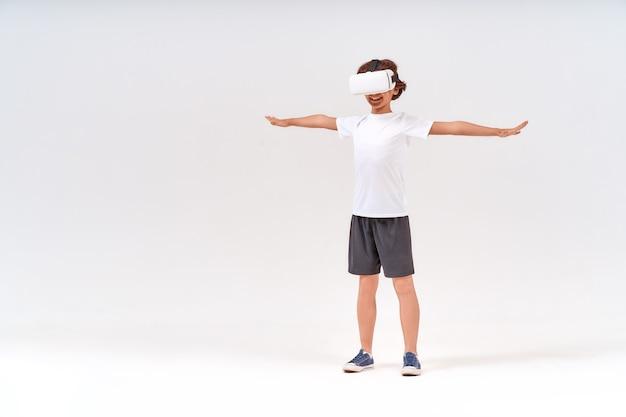 Tecnologia vr a figura intera di un adolescente in abiti sportivi che indossa occhiali per la realtà virtuale o d
