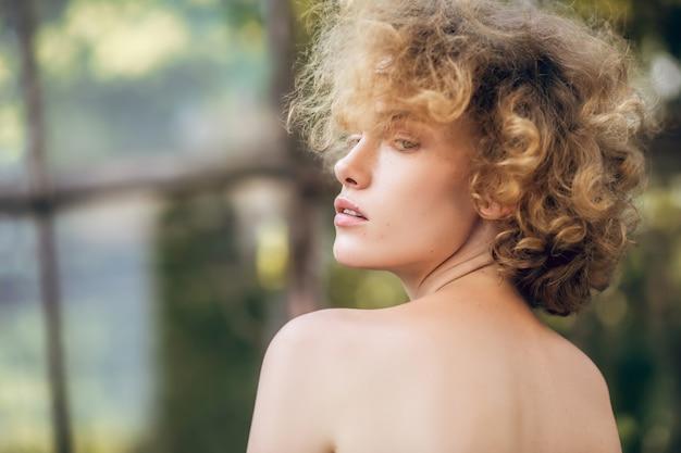 Vulnerabilità. colpo alla testa di una giovane donna seria con le spalle nude