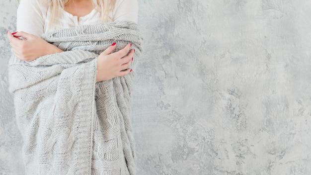 Natura femminile vulnerabile e sensibile. donna in coperta lavorata a maglia a mano calda grigia.