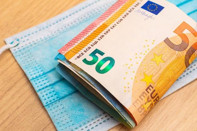 Un mucchio di banconote in euro su una maschera chirurgica blu per il concetto di economia durante la pandemia di covid