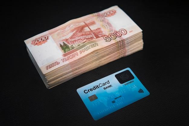 Un batuffolo di denaro da rubli russi e una carta bancaria di plastica si trovano su uno sfondo nero banconote di carta e rubli russi.