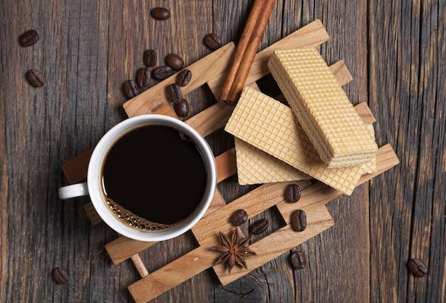 Wafer e tazza di caffè caldo per colazione su fondo di legno scuro