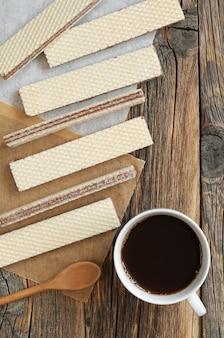 Wafer che riempiono cioccolato e tazza di caffè sulla vista rustica del piano d'appoggio