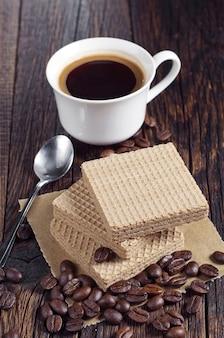 Wafer con latte condensato caramellato e tazza di caffè caldo su tavola in legno rustico