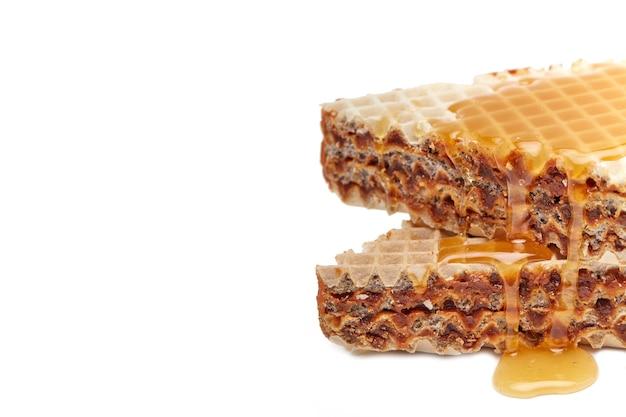 Torta di waffle versata con miele su un piatto bianco su sfondo bianco con un posto per copiare il testo
