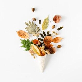 Cono di cialda con bouquet di foglie secche autunnali su bianco