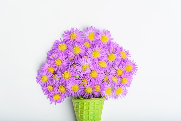 Cono di cialda con fiori aster alpino su uno sfondo bianco concetto 8 marzo, san valentino.