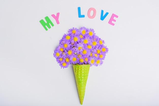 Cono di cialda con fiori aster alpino su uno sfondo bianco concetto san valentino, amore mio.