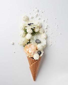Cono di cialda con bouquet di fiori e meringhe su sfondo bianco, piatto, vista dall'alto