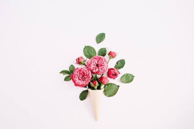Cono di cialda con bouquet di rose rosse su sfondo rosa pastello pallido. lay piatto