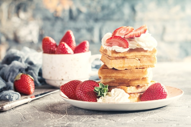Dessert waffle con salsa di panna e fragole su grigio