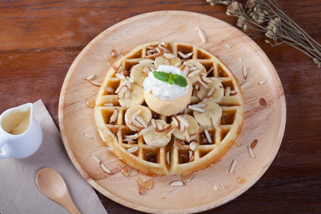 Waffle con banana e gelato alla vaniglia sulla crema di frusta e menta piperita cospargere con mandorle intorno.