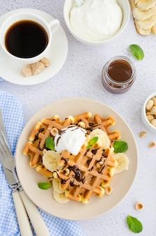 Waffle con banana fresca, nocciole, salsa al cioccolato e panna montata su un piatto