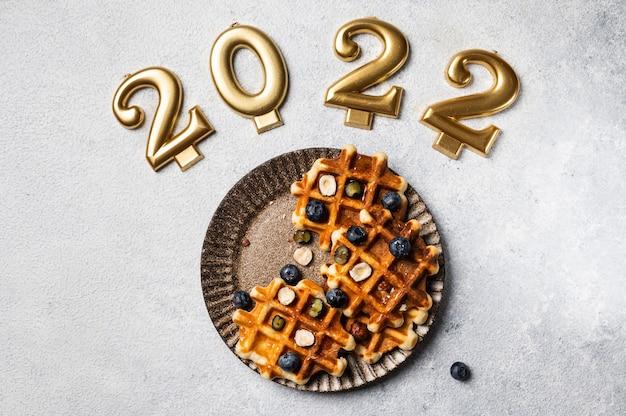 Cialde con miele e mirtilli per natale. piatto di capodanno. 2022 anno. piatto per bambini per natale. waffle vista dall'alto