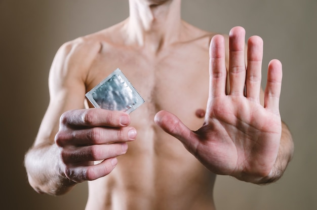 In vita, un attraente uomo nudo in jeans neri tiene in mano un preservativo e l'altra mano è aperta