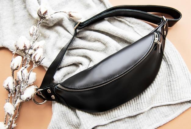 Marsupio realizzato in pelle nera e pianta di cotone su una superficie lavorata a maglia grigia.