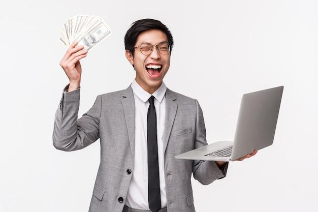 Mezzo busto di eccitato, fortunato bel ragazzo asiatico ricco, l'imprenditore ha ottenuto i suoi primi soldi, vendendo o investendo in società, stringendo la mano con dollari, grosse somme di denaro, tenendo laptop e trionfando