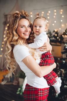 Mezzo busto di madre felice con il suo bambino carino in posa alla vigilia di natale