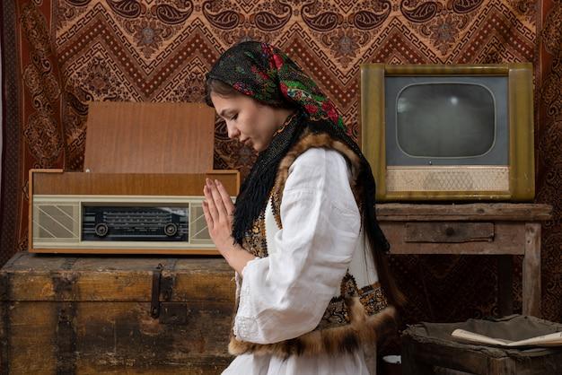 Mezzo busto foto di una giovane donna in abito bianco nazionale e fazzoletto nero che prega con gli occhi chiusi