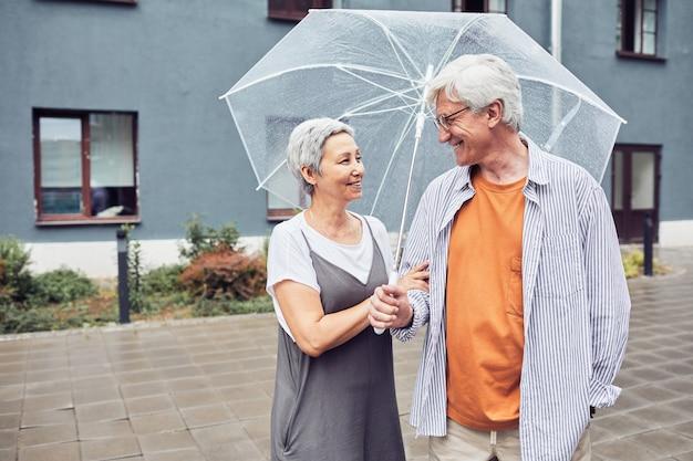 Ritratto in vita di una coppia senior attiva che si guarda mentre si gode una vacanza in città, copia spazio