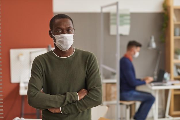 Mezzo busto ritratto di adulto afro-americano uomo che indossa la maschera e guardando la fotocamera in piedi con le braccia incrociate in ufficio, copia spazio