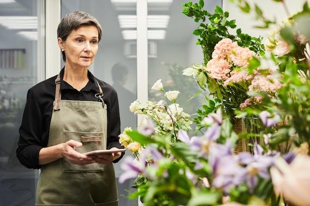 Mezzo busto ritratto di fiorista femmina adulta che fa l'inventario delle scorte mentre si lavora in un negozio di fiori piccolo b...