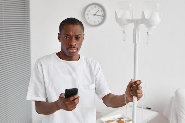 Ritratto in vita di un uomo afro-americano che tiene il supporto per gocciolamento iv durante il trattamento in ospedale e guarda la telecamera, copia spazio