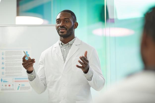 Ritratto in vita di un uomo afro-americano in piedi davanti alla lavagna mentre fa una presentazione durante un seminario medico al college, copia spazio