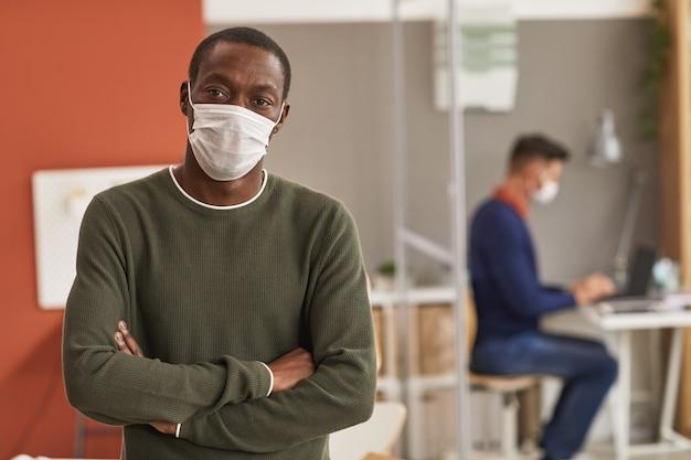 Mezzo busto ritratto di uomo afro-americano che indossa la maschera e guardando la fotocamera mentre in piedi con le braccia incrociate in ufficio, copia dello spazio