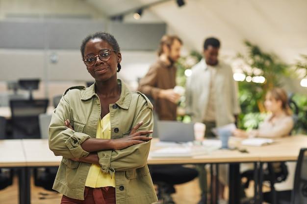 Mezzo busto ritratto di donna afro-americana mentre posa con fiducia in piedi con le braccia incrociate in ufficio moderno con persone che lavorano in superficie, spazio di copia
