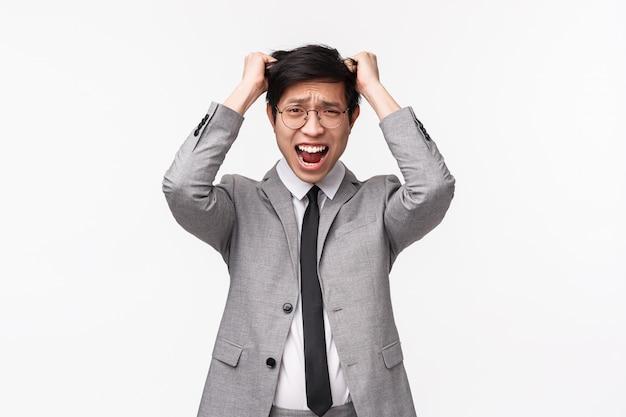 Mezzo busto ritratto di allarmato e imbarazzato giovane dirigente maschio asiatico che non riesce a rispettare la scadenza, ha fatto un grosso errore e si è strappato i capelli dalla testa stressata, urlando facendo una smorfia triste sul muro bianco