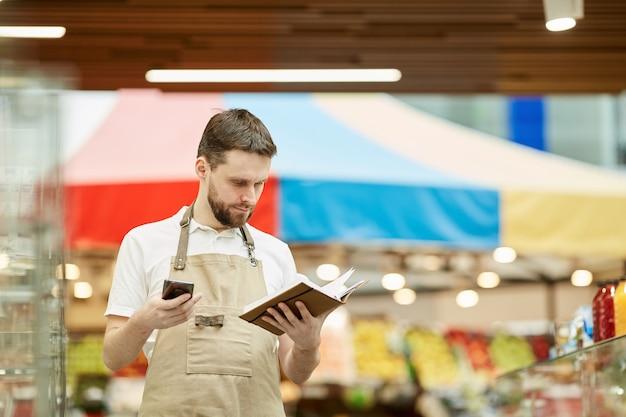 Mezzo busto ritratto di uomo barbuto che chiama da smartphone mentre si fa il conteggio dell'inventario nel supermercato