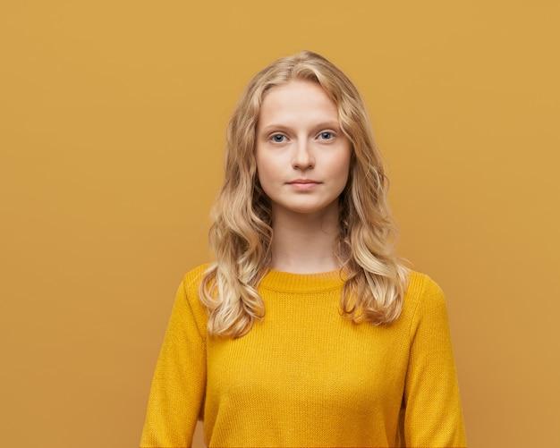 Mezzo busto ritratto di bella giovane donna scandinava bionda intelligente seria su giallo brillante