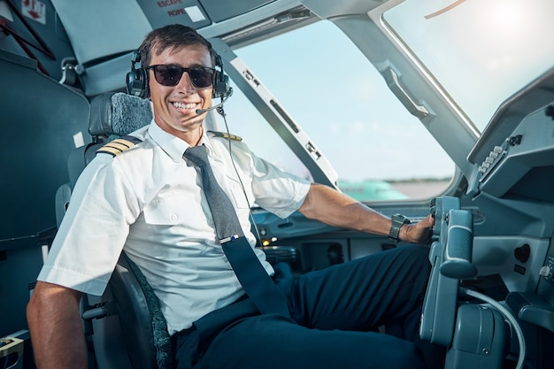 Mezzo busto ritratto di un giovane allegro con gli occhiali e gli auricolari seduto in cabina di pilotaggio e pronto per il volo