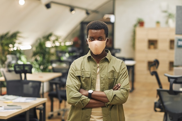 Mezzo busto ritratto di fiducioso afro-americano uomo che indossa la maschera in ufficio e in piedi con le braccia incrociate in ufficio, copia dello spazio