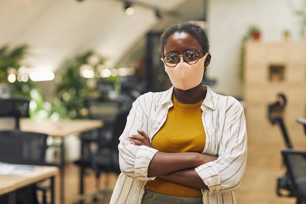 Mezzo busto ritratto di fiduciosa donna afro-americana che indossa la maschera in ufficio e in piedi con le braccia incrociate in ufficio, copia spazio