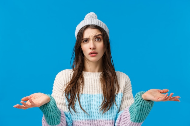 Ritratto di giovane donna confusa in maglione invernale, cappello, non capisco