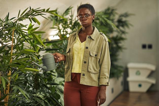 Mezzo busto ritratto di donna afro-americana contemporanea che innaffia le piante in ufficio e copia spazio