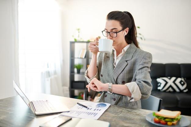Mezzo busto ritratto di donna d'affari contemporanea guardando orologio mentre si lavora in ufficio, copia spazio