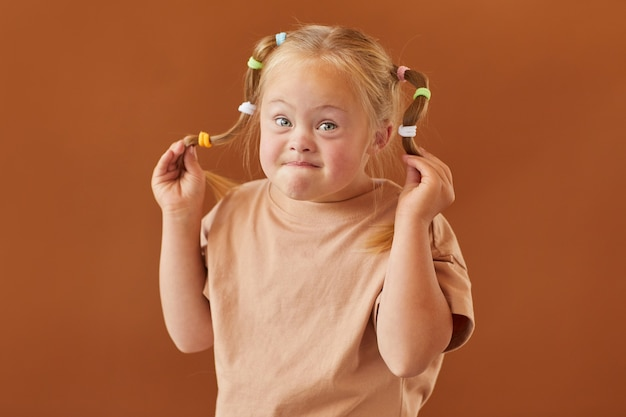 Mezzo busto ritratto di ragazza bionda carina con sindrome di down che fa i fronti alla macchina fotografica mentre levandosi in piedi contro la superficie marrone normale in studio, spazio della copia