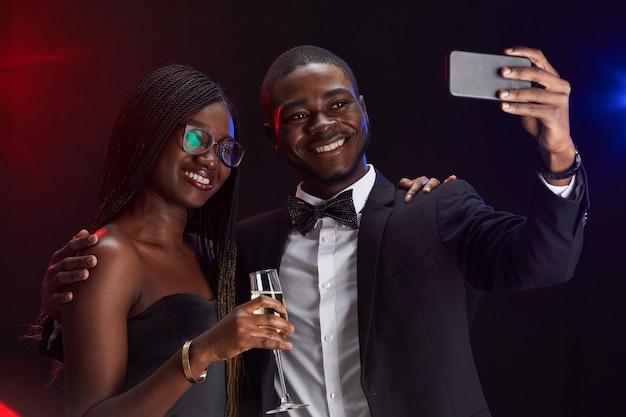 Mezzo busto ritratto di elegante coppia afro-americana che cattura foto selfie mentre si gode la festa