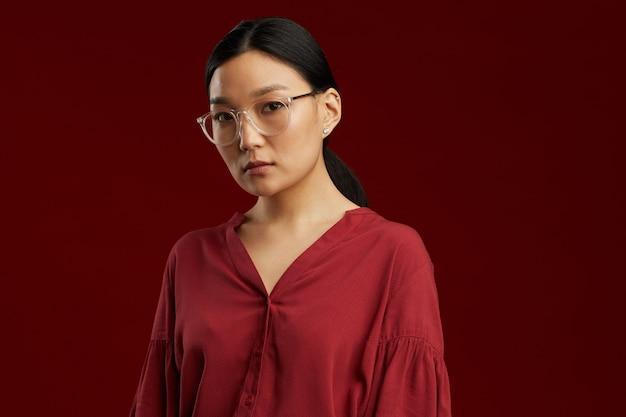 Mezzo busto ritratto di elegante donna asiatica in posa contro il muro marrone
