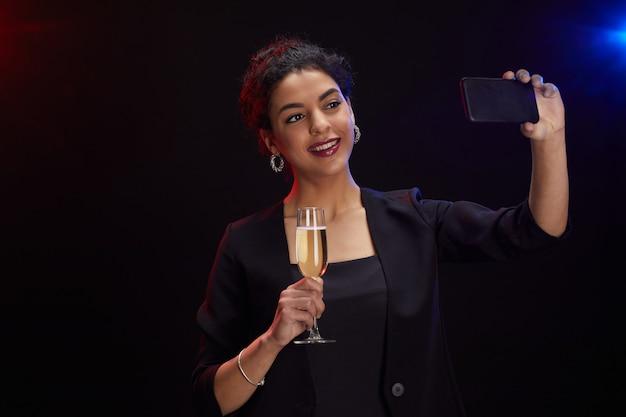 Mezzo busto ritratto di elegante donna mediorientale con bicchiere di champagne e scattare foto selfie mentre in piedi su sfondo nero alla festa, copia spazio