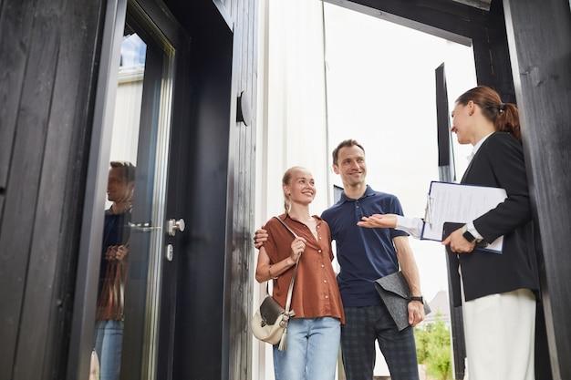 Mezzo busto ritratto di agente immobiliare femminile che incontra una giovane coppia in piedi sulla porta mentre acquista una nuova casa, copia spazio