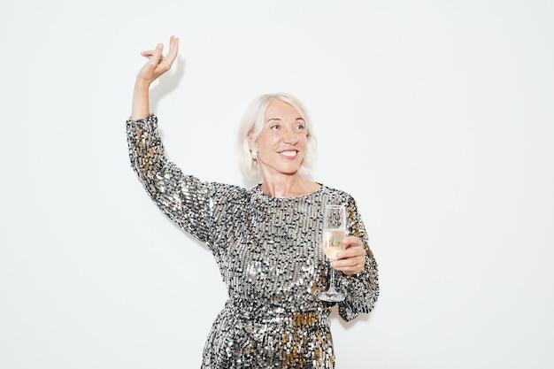 Mezzo busto ritratto di una donna matura affascinante che balla su sfondo bianco alla festa, girato con il flash