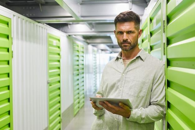 Mezzo busto ritratto di bell'uomo barbuto che tiene tavoletta digitale mentre si è in piedi da unità di archiviazione automatica, copia dello spazio