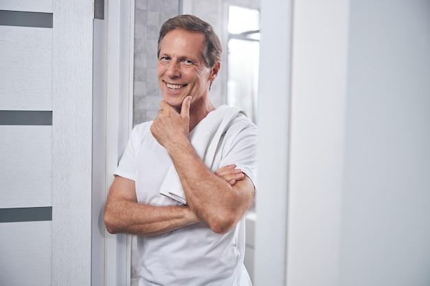 Ritratto in vita di un uomo felice con una maglietta che si appoggia il mento sulla mano