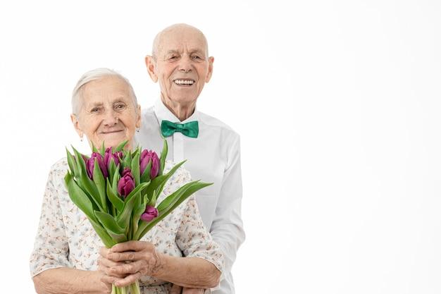 Mezzo busto ritratto delle vecchie coppie sorridenti felici con un mazzo di fiori